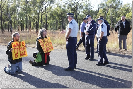 Queensland Police prepare to arrest peace activists Jim Dowling & Ciaron O' Reilly for blocking military vehicles access to the Talisman Sabre military training facility.