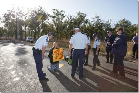 Police arresting Jim Dowling for blocking military access to the Talisman Sabre training facility.