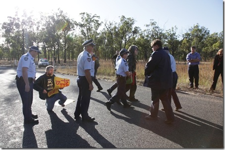 Police arresting Anti-War activists Jim Dowling and Ciaron O' Reilly for blocking military access to the Talisman Sabre training facility