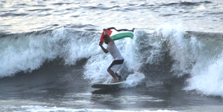 surfing at byron with palestinian flag