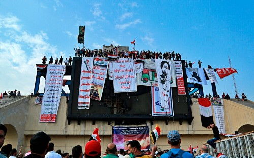 "In this Oct. 30, 2019, photo, Iraqi anti-government protesters hang their demands and slogans while standing on a building near Tahrir Square, Baghdad, Iraq. An abandoned building in central Baghdad has emerged as the epicenter of anti-government protests in Iraq, with hundreds holed up inside. The Saddam Hussein-era building known as the ""Turkish Restaurant"" overlooks Tahrir Square, the Tigris River and the Green Zone, and protesters who took it over on Oct. 25 have sworn not to leave it. (AP Photo/Hadi Mizban)"